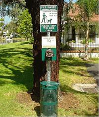 Sign with Pet Waste Disposal instructions above a bag dispenser and trash receptacle