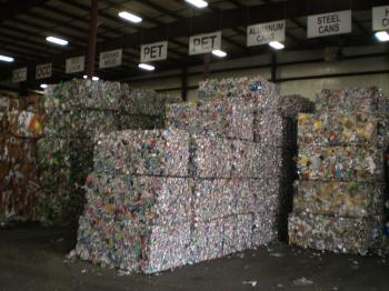 Bundles of recycled material stacked in a warehouse under signs indicating what they are.