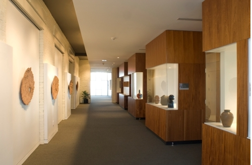 A hallway with art exhibits encased in glass on one side and hanging sculptures on the other